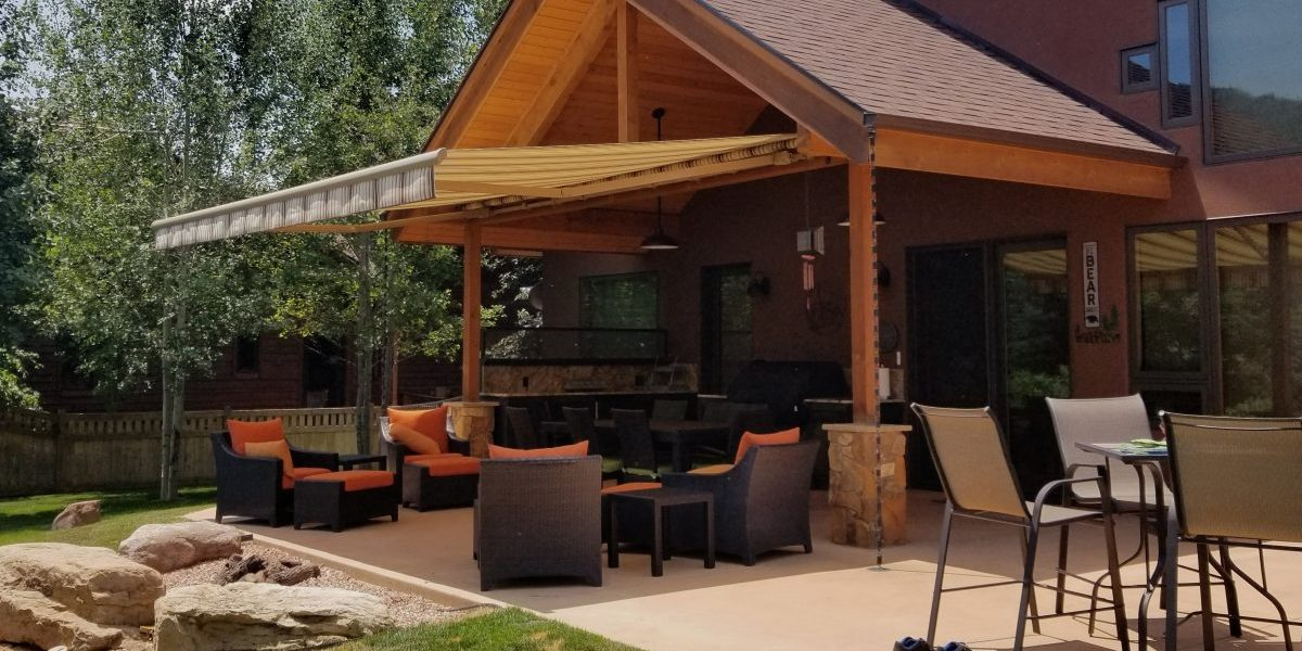 A patio with a motorized awning providing shade during a hot summer day.