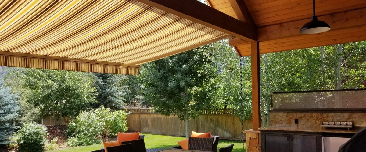 Back patio with a motorized awning extended in Broomfield, co